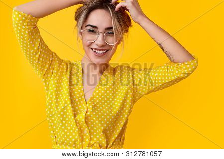 poster of Happy Young Woman In Spotted Dress Friendly Smiling And Touching Blond Hair While Standing Against V