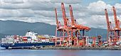 Container Ship Unloads In The Port Of Vancouver, Red Sea Cranes And Colorful Containers On The Backg poster