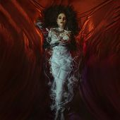 Vampire Halloween Woman portrait. Beauty Sexy Vampire Girl lying in red satin fabric. Vampire makeup poster