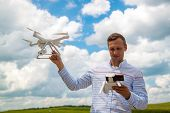 Young Man Controlling Drone In Field. Drone Operator Holding A Transmitter. poster