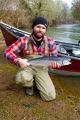 stock photo of steelhead  - A steelhead fisherman holds his trophy fish by his boat and the river in Oregon - JPG