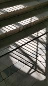 Abstract Striped Shadows From Window Lattice On Grey Stone Steps In Bright Sunlight. Staircase In Ol poster