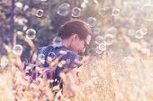 Woman In Sunset. Lifestyle Concept. Hipster Woman Relaxing In Sunset In Meadow With Foam Bubbles. He poster