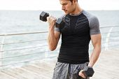 Cropped image of a strong serious concentrated young sports man outdoors at beach make exercises for poster