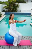 Front view of fit mixed-race woman exercising with resistance band while sitting on a exercise ball  poster