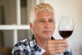Senior man holding and looking through a glass of red wine. Old man tasting red wine at home. Retire poster