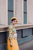 Stylish Young Woman In A Yellow Beret Is Standing On The Street On A Urban Background With Different poster