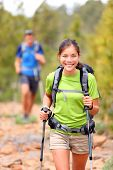 Hiker woman. Hiking asian woman walking with hiking poles and hiking backpack smiling happy outdoors