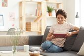 Happy Pretty Young Woman In Casual Outfit Sitting On Sofa At Home And Using Tablet While Browsing In poster