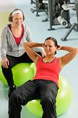 stock photo of personal trainer  - Fitness center senior woman with trainer exercising on swiss ball - JPG