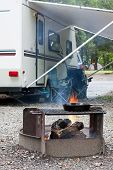 stock photo of trailer park  - An outdoor grill at a Pennsylvania State Park with a camping trailer in the background - JPG