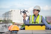 Asian Engineer Man Working With Drone And Working Tools At Construction Site. Male Worker Using Unma poster