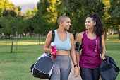 Young female friends talking after workout routine in park. Two curvy women in a conversation holdin poster