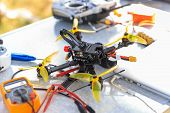 A Fpv High-speed Racing Drone Copter And Remote Telemetry Controller Lying On The Table poster
