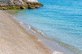 Amazing View On The Seaside Beach With Azure Water, Yellow Sand And A Small Rock In The Corner Of Th poster