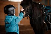 Closeup Of A Kid Stroking A Horse. The Boy Is Preparing To Learn Pony Riding In The Cold Season. Hip poster