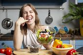 Young Cheerful Girl Prepares A Vegetarian Salad In The Kitchen, She Tastes Olive, The Process Of Pre poster