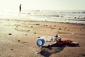Plastic Bottle And Trash Lying On The Shore Of The Beach And Polluting The Sea And The Marine Life,  poster