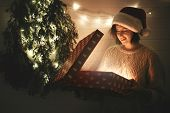 Stylish Happy Girl In Santa Hat And Cozy Sweater Opening Christmas Gift Box With Magic Light In Dark poster