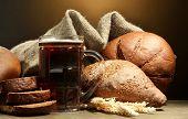Постер, плакат: кружка кваса и ржаной хлеб с ушами на деревянный стол на коричневый фон