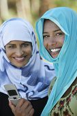 picture of dupatta  - Portrait of two Asian female friends in headscarf holding mobile phone - JPG