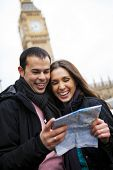 Couple of tourists in London holding a map in a cloudy day.