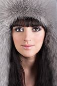 Portrait of young beautiful woman in winter furry hat poster