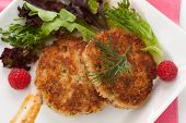 stock photo of cooked crab  - Two crab cakes appetizer garnished with spicy sauce green salad and raspbery - JPG