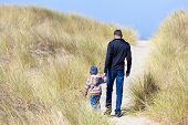 stock photo of dune grass  - family of father and son walking on the sandy beach trail in bandon oregon - JPG