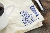 go the extra mile - motivational slogan on a napkin with a cup of coffee