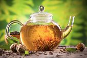Teapot with blooming tea on blur green background