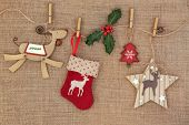 Old fashioned christmas decorations hanging on a line with holly over hessian background.
