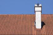 stock photo of red roof tile  - Traditional red tile on roof against the blue sky - JPG