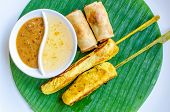 pic of gai  - Vegetables spring roll and chicken satay on banana leaf - JPG