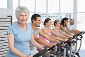 stock photo of senior class  - Group portrait of happy people working out at exercise bike class in gym - JPG