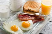 stock photo of scrambled eggs  - eggs with bacon for breakfast - JPG