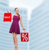 beauty, fashion, shopping and happy people concept - young woman in purple dress and high heels with