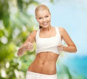 diet and fitness concept - beautiful sporty woman showing thumbs up and her abs