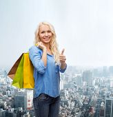 retail, gesture and sale concept - smiling woman with many shopping bags showing thumbs up