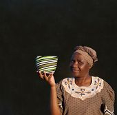 pic of zulu  - Traditional South African Zulu woman basket sales woman on blackboard background - JPG