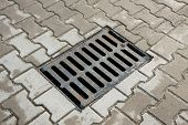 stock photo of manhole  - sewer drain on the sidewalk in the city - JPG
