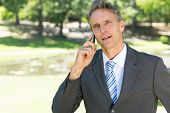 Portrait of confident businessman talking on smart phone in park