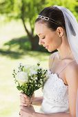 Side view of shy bride holding flower bouquet in garden