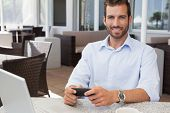 Happy businessman sending a text at table in patio of restaurant