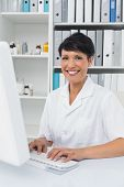Portrait of a confident smiling female doctor using computer at medical office