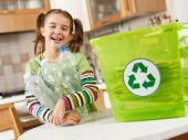 picture of recycled paper  - Girl looking at camera and holding plastic bottles for recycling - JPG