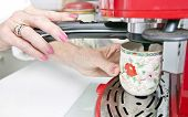 foto of coffee crop  - Cropped image of woman dispensing coffee from machine in kitchen - JPG