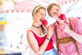 stock photo of national costume  - Couple visiting together Bavarian fair in national costume eating  candy apple - JPG