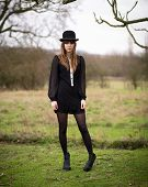 pic of nylons  - Portrait of a beautiful young woman wearing a black dress nylons boots and a bowler hat standing in a country farm field hair blowing in the wind - JPG