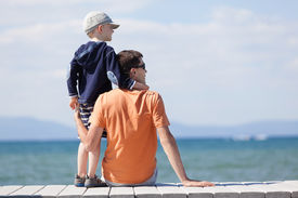 pic of dock a lake  - cheerful family of two sitting at the dock during vacation at lake tahoe california usa - JPG
